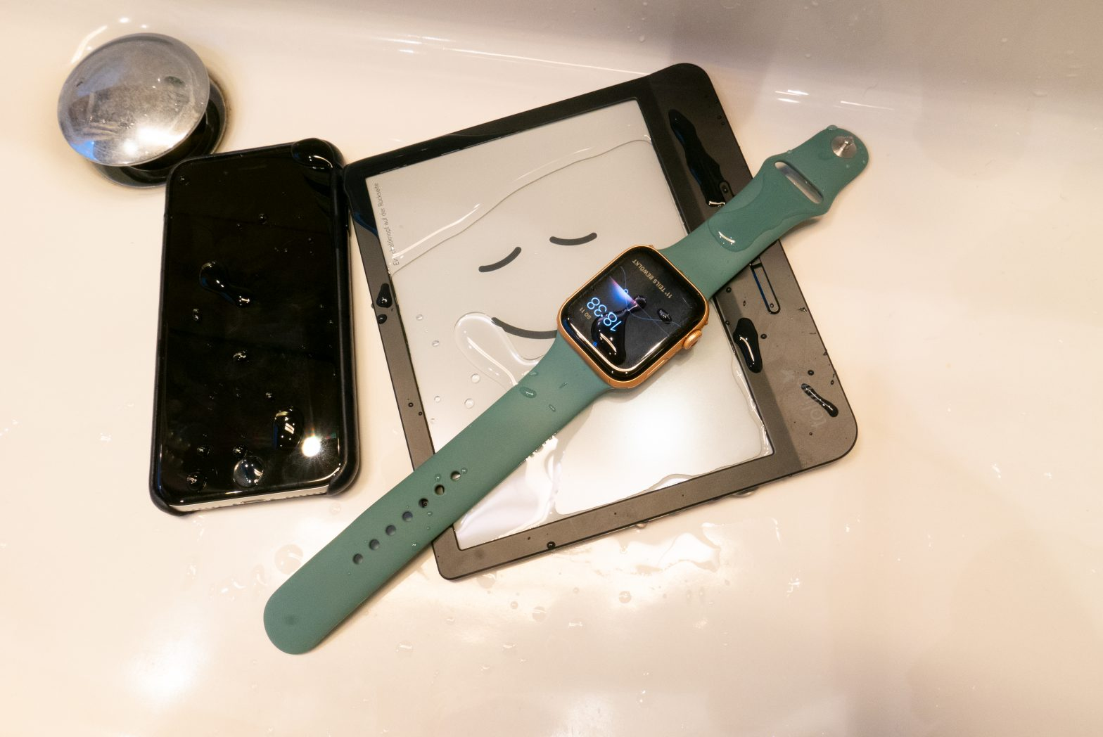 An iPhone, Apple Watch and Tolino e-book reader spattered with water.